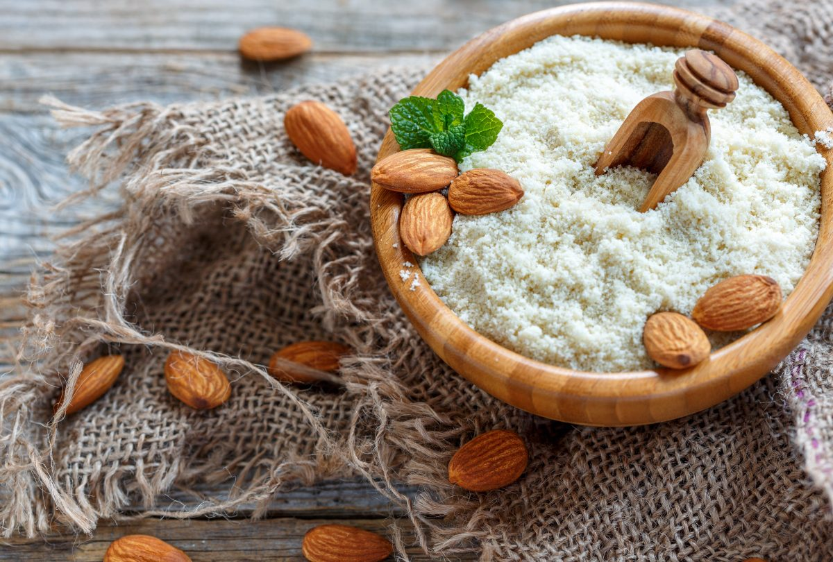 Mint and almond flour in a bowl on a wooden table with sacking.